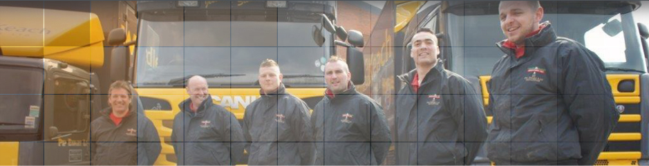 Close up of work colleagues by lorries